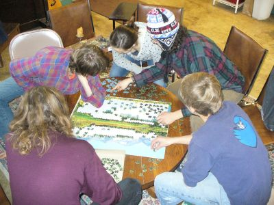 Jigsaw puzzling at Our Community Place in Harrisonburg, Virginia, by Artaxerxes, via Wikipedia.