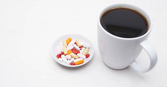 cup-of-coffee-and-saucer-of-pills-on-white-background-close-up